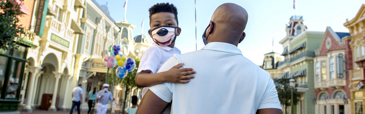 dad holding son wearing mickey mouse mask
