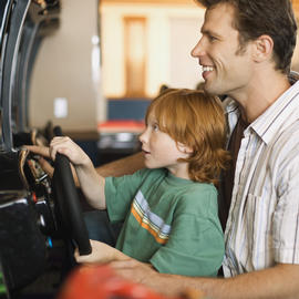 Father and son playing racing video game