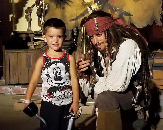 little boy posing for photo with captain jack sparrow