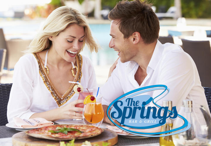 young couple eating pizza and drinking cocktails outside