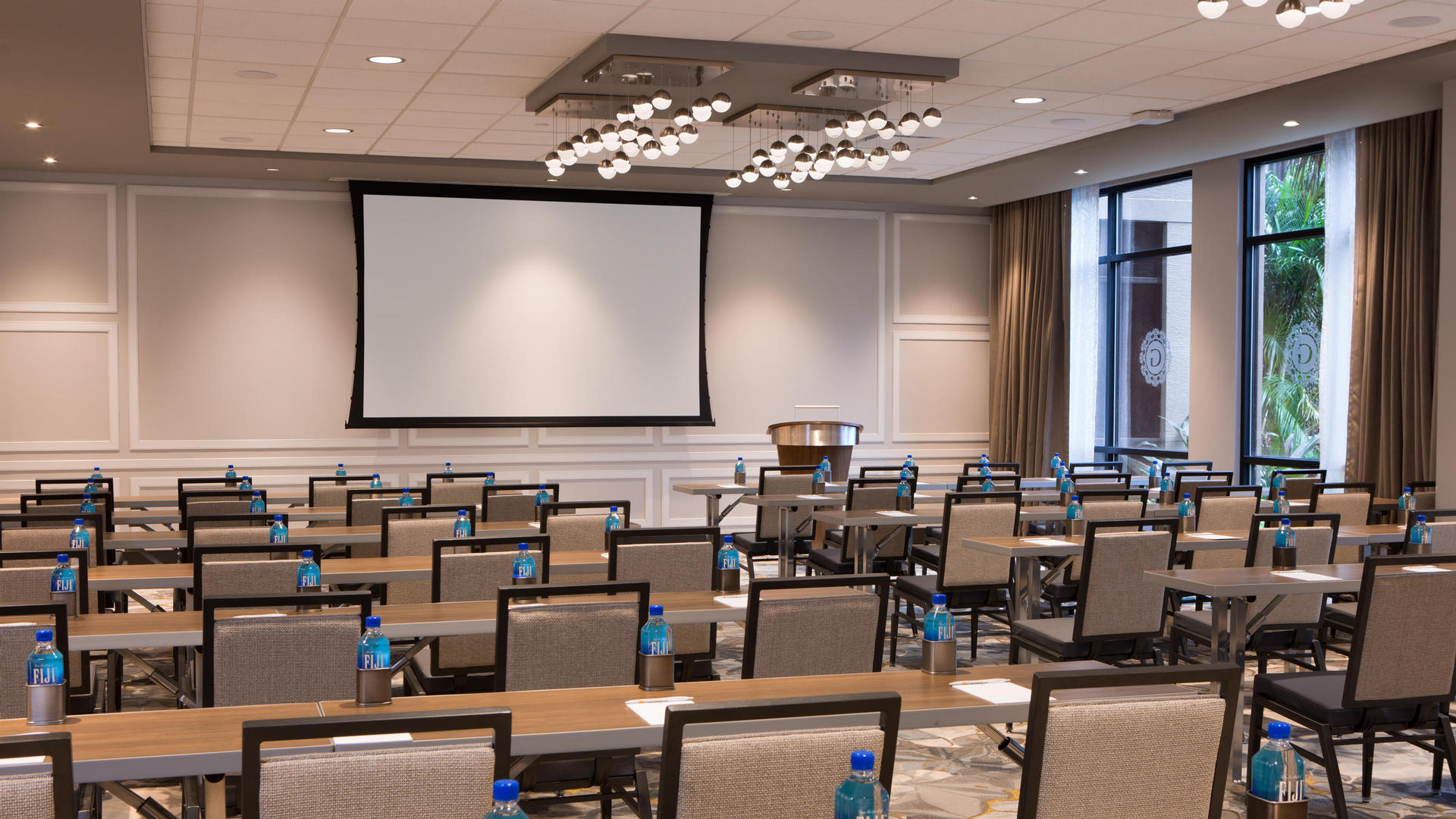 large meeting room with tables and a projection screen at the front