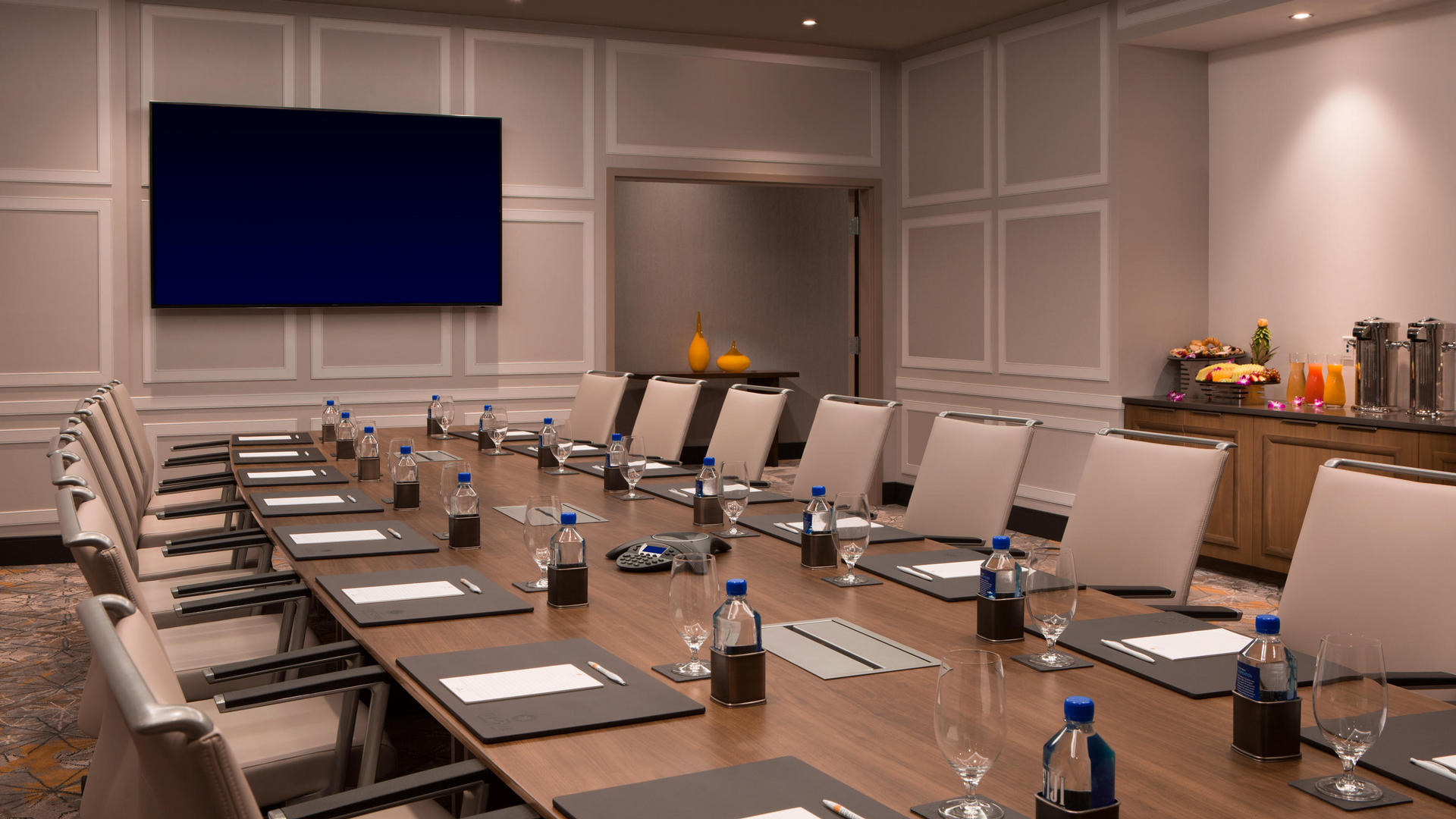 large boardroom with meeting table and television on the wall