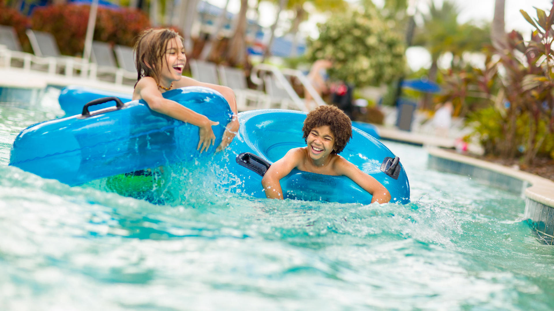 kids splashing in blue tubes in the lazy river